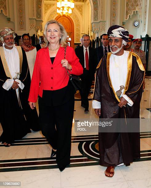 US Secretary of State Hillary Clinton walks with Sultan Qaboos bin Said upon her arrival at the sultan's palace for lunch in Muscat on October 19...