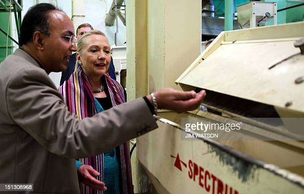 US Secretary of State Hillary Clinton watches coffee beans come out of a sorter during a tour of the Timor Coffee Cooperative in Dili on September 6...