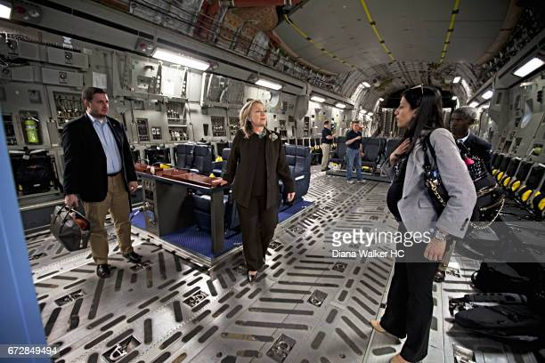 Secretary of State Hillary Rodham Clinton confers with top aides Huma Abedin and Philippe Reines minutes before exiting the plane on October 18 2011...