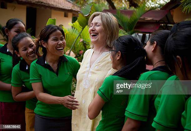US Secretary of State Hillary Rodham Clinton greets children during a tour of the Siem Reap Center a shelter run by AFSEIP that provides...