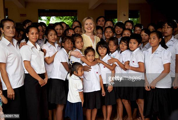 US Secretary of State Hillary Rodham Clinton posses with children during a tour of the Siem Reap Center a shelter run by AFSEIP that provides...