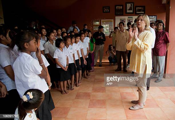 US Secretary of State Hillary Rodham Clinton talks with children during a tour of the Siem Reap Center a shelter run by AFSEIP that provides...