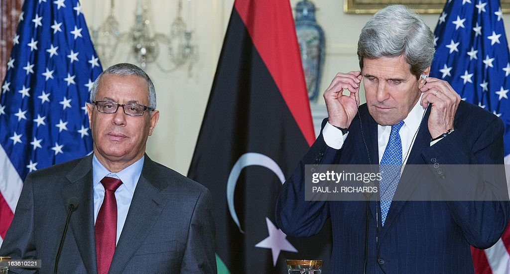 US Secretary of State John Kerry adjusts his translation headsets as Libyan Prime Minister Ali Zeidan(L), delivers remarks in the to the media after their private bilateral meeting March 13, 2013, at the US Department of State in Washington, DC. AFP Photo/Paul J. Richards