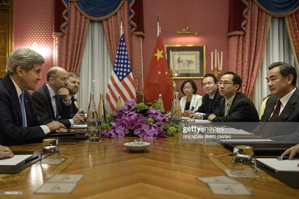 US Secretary of State John Kerry and Chinese Foreign Minister Wang Yi wait before the start of a meeting at the Beau Rivage Palace Hotel on March 29...