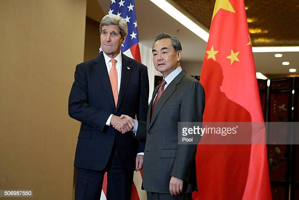 S Secretary of State John Kerry and Chinese Foreign Minister Wang Yi shake hands before their bilateral meeting at the Ministry of Foreign Affairs...