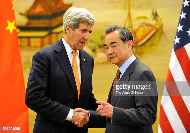 US Secretary of State John Kerry and Chinese Foreign Minister Wang Yi shake hands during a press conference following their bilateral meeting on...