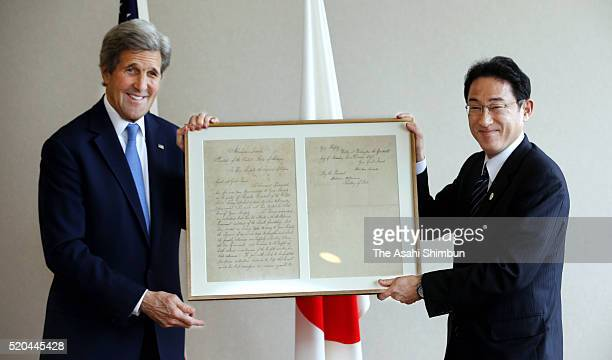 US Secretary of State John Kerry and Japanese Foreign Minister Fumio Kishida pose with a replica of the letter which US President Abraham Lincoln...