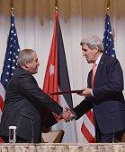 US Secretary of State John Kerry and Jordanian Foreign Minister Nasser Judeh exchange documents after signing a memorandum of understanding between...