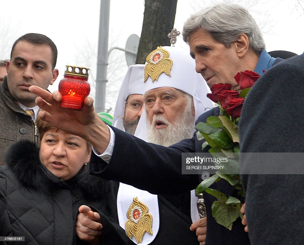 US Secretary of State John Kerry (R) and Ukraine's Patriarch Filaret speak as Kerry sets a candle to the Shrine of the Fallen, an homage to anti-government protesters, who died during the February clashes with anti-riot policemen, in Kiev on March 4, 2014. Kerry arrived in Kiev for talks with Ukraine's new interim government, amid an escalating crisis in Crimea.