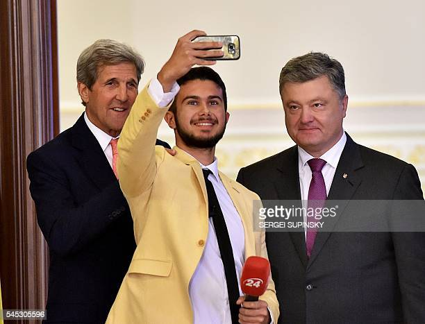 US Secretary of State John Kerry and Ukrainian President Petro Poroshenko pose for selfie with a Ukrainian journalist after their press conference in...