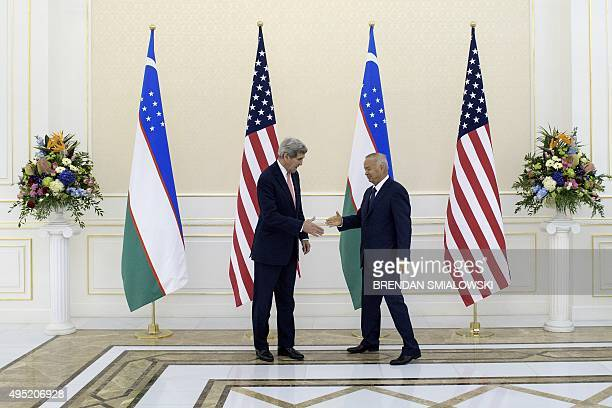US Secretary of State John Kerry and Uzbek President Islam Karimov shake hands before a meeting at the Palace of Forums on the President's...