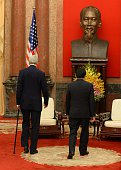 US Secretary of State John Kerry and Vietnamese President Truong Tan Sang move toward their seats in front of a bust of late president Ho Chi Minh...