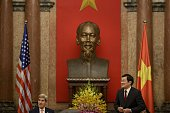 US Secretary of State John Kerry and Vietnam's President Truong Tan Sang wait for the start of a meeting at the Presidential Palace in Hanoi on...