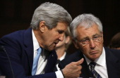 S Secretary of State John Kerry confers with US Defense Secretary Chuck Hagel as they testify before the Senate Foreign Relations Committee on the...