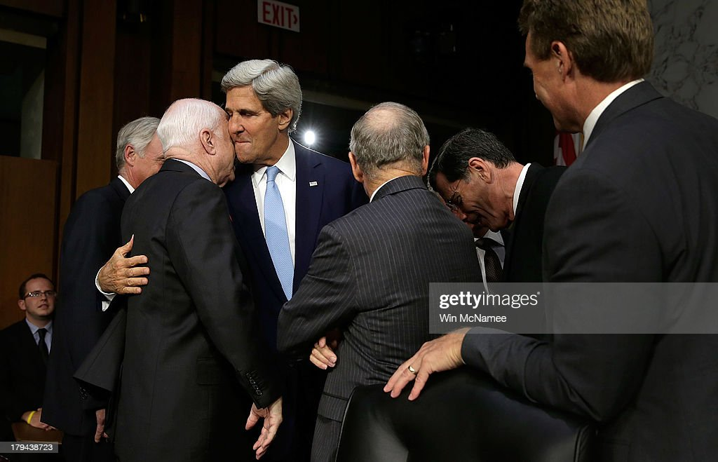 U.S. Secretary of State <a gi-track='captionPersonalityLinkClicked' href=/galleries/search?phrase=John+Kerry&family=editorial&specificpeople=154885 ng-click='$event.stopPropagation()'>John Kerry</a> (3rd L) embraces Sen. <a gi-track='captionPersonalityLinkClicked' href=/galleries/search?phrase=John+McCain&family=editorial&specificpeople=125177 ng-click='$event.stopPropagation()'>John McCain</a> (R-AZ) (2nd L) before Kerry testified before the Senate Foreign Relations Committee on the topic of 'The Authorization of Use of Force in Syria' September 3, 2013 in Washington, DC. U.S. President Barack Obama is attempting to enlist the support of members of the U.S. Congress for military action against the Syrian government for using chemical weapons against its own people last month.