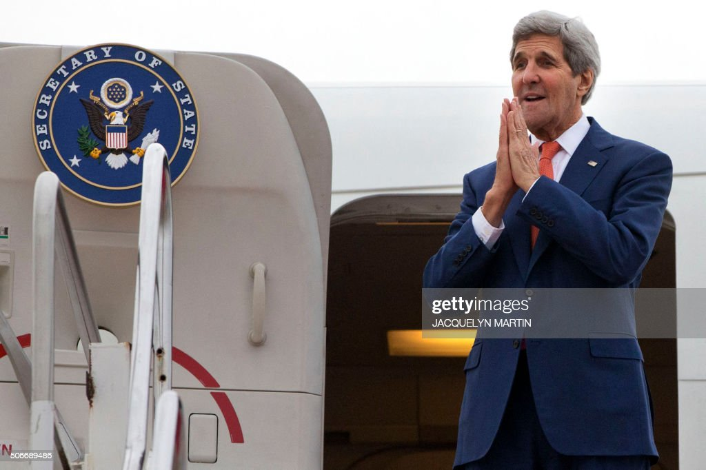 US Secretary of State John Kerry gestures as he says goodbye while boarding his plane in Vientiane before leaving for Phnom Penh on January 25 2016...