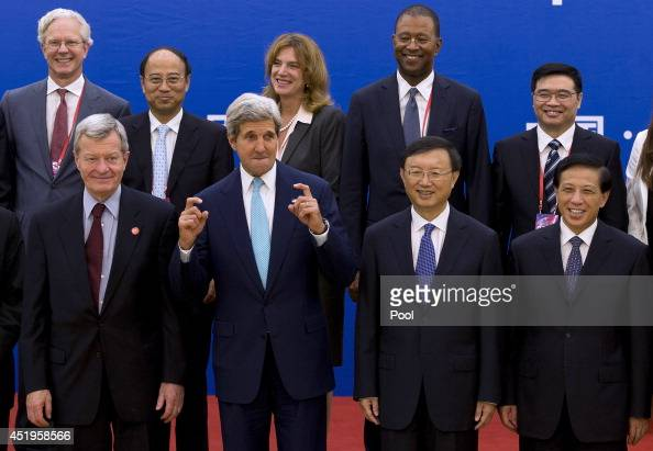 S Secretary of State John Kerry gestures next to Chinese State Council Yang Jiechi as they pose fro a group photo with delegation from both countries...