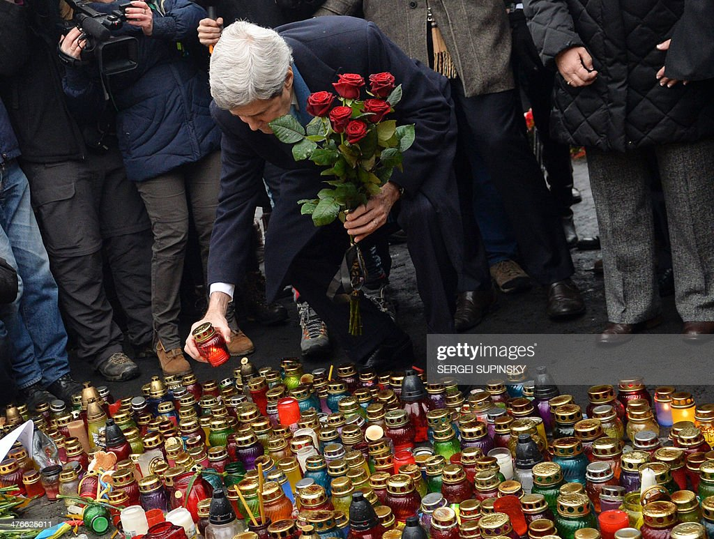 US Secretary of State John Kerry, holding a bouquet of red roses, sets a candle to the Shrine of the Fallen, a homage to anti-government protesters zho died during the February clashes with anti-riot policem in Kiev on March 4, 2014. US Secretary of State John Kerry arrived in Kiev Tuesday for talks with Ukraine's new interim government, amid an escalating crisis in Crimea. His visit came as the United States said it would provide $1 billion to financially-stricken Ukraine as part of an international loan.