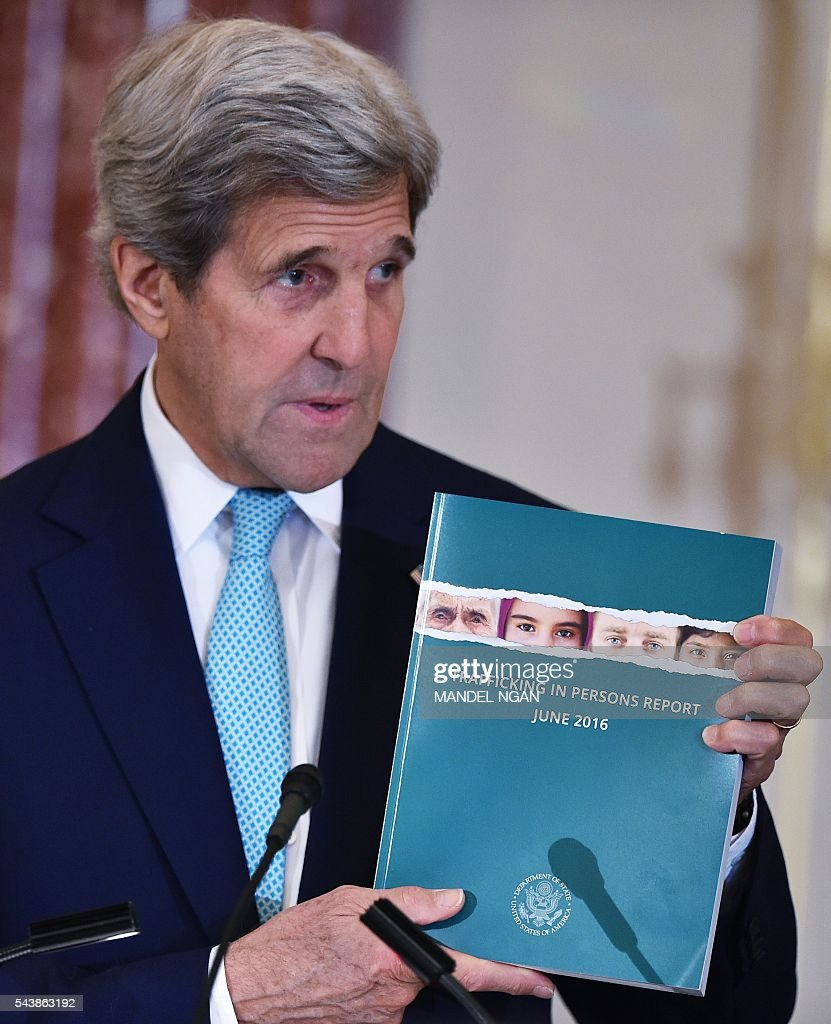 US Secretary of State John Kerry holds a copy of the 2016 Trafficking in Persons Report during its release on June 30, 2016 at the State Department in Washington, DC . / AFP / MANDEL