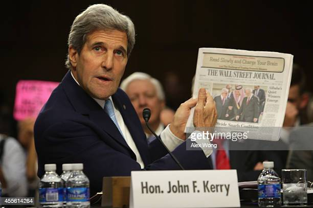 S Secretary of State John Kerry holds up a copy of the Wall Street Journal as he testifies during a hearing before the Senate Foreign Relations...