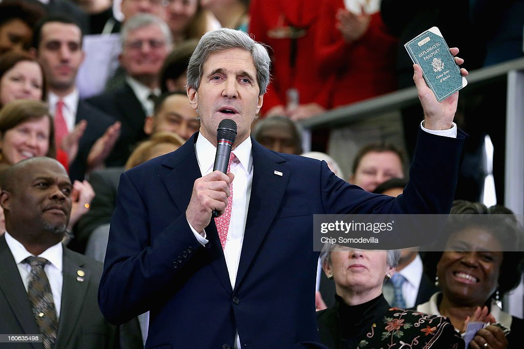 U.S. Secretary of State John Kerry holds up his first diplomatic passport he received as an 11-year-old boy while making remarks to employees on his first day at the State Department February 4, 2013 in Washington, DC. Kerry was issued the passport when he traveled with his father, a foreign service diplomat, to post-WWII Germany.