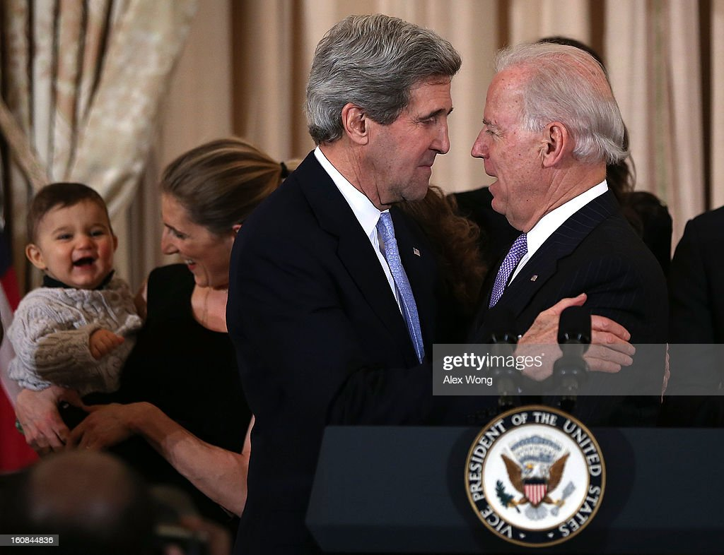 U.S. Secretary of State John Kerry (2nd R) hugs Vice President Joseph Biden (R) after Kerry's ceremonial swearing in at the State Department February 6, 2013 in Washington, DC. Kerry was officially sworn in on February 1 at the U.S. Capitol as the 68th Secretary of State, succeeding Hillary Clinton.