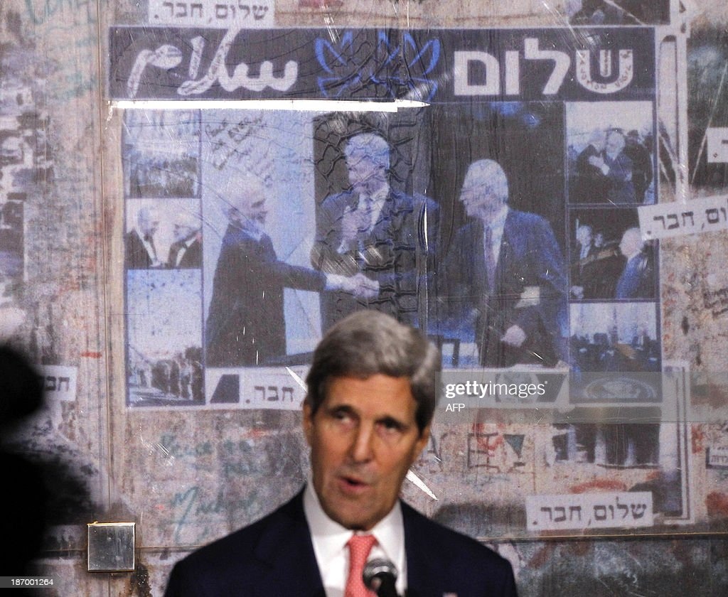 U.S. Secretary of State John Kerry is pictured in front of a photo showing U.S. President Bill Clinon, Jordan's King Hussein and Yitzhak Rabin, as Kerry marks the 18th anniversary of Rabin's assassination in Tel Aviv, on November 5, 2013.