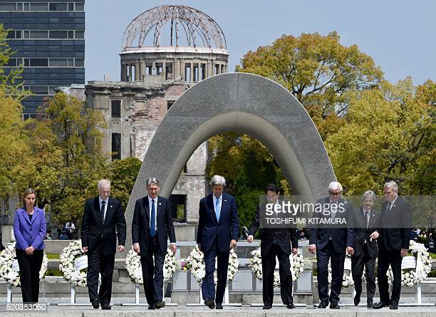 US Secretary of State John Kerry is shown the way by Japan's Foreign Minister Fumio Kishida after laying a wreath with European Union High...