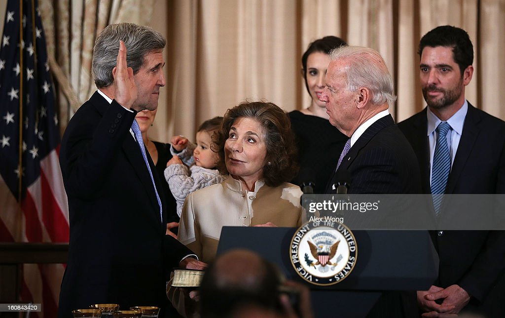 U.S. Secretary of State <a gi-track='captionPersonalityLinkClicked' href=/galleries/search?phrase=John+Kerry&family=editorial&specificpeople=154885 ng-click='$event.stopPropagation()'>John Kerry</a> (L) is sworn in by Vice President <a gi-track='captionPersonalityLinkClicked' href=/galleries/search?phrase=Joseph+Biden&family=editorial&specificpeople=206897 ng-click='$event.stopPropagation()'>Joseph Biden</a> (R) as Kerry's wife Teresa Heinz (C) holds a bible during a ceremonial swearing in at the State Department February 6, 2013 in Washington, DC. Kerry was officially sworn in as the 68th Secretary of State succeeding Hillary Clinton on February 1 at the U.S. Capitol.