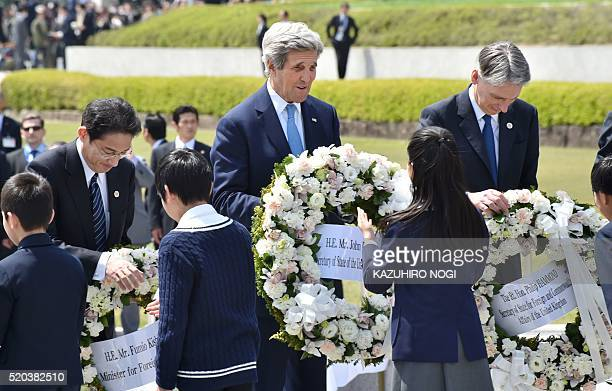 US Secretary of State John Kerry Japan's Foreign Minister Fumio Kishida and British Foreign Secretary Philip Hammond receive wreaths to offer at the...