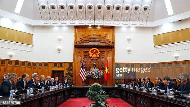 Secretary of State John Kerry listens to Prime Minister Nguyen Xuan Phuc speaks at the Office of the Government during their meeting in Hanoi on...