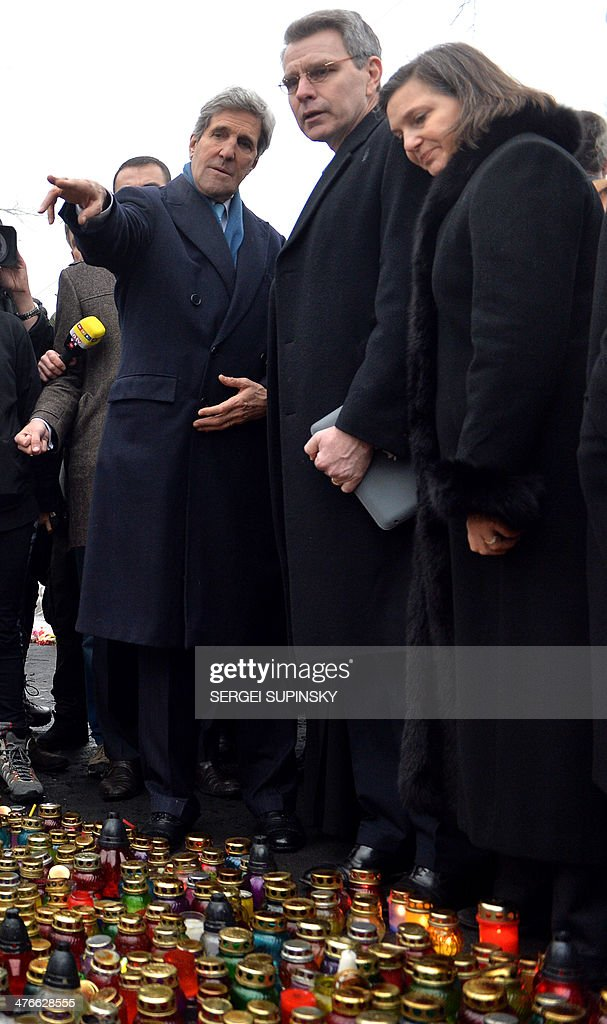 US Secretary of State John Kerry points his finger as he stands with US Assistant Secretary of State for Europe Victoria Nuland (R) and US embassy in Ukraine Geoffrey Pyatt (C) in front of the Shrine of the Fallen, an homage to anti-government protesters who died during the February clashes with anti-riot policemen in Kiev, on March 4, 2014. US Secretary of State John Kerry arrived in Kiev Tuesday for talks with Ukraine's new interim government, amid an escalating crisis in Crimea. His visit came as the United States said it would provide $1 billion to financially-stricken Ukraine as part of an international loan.