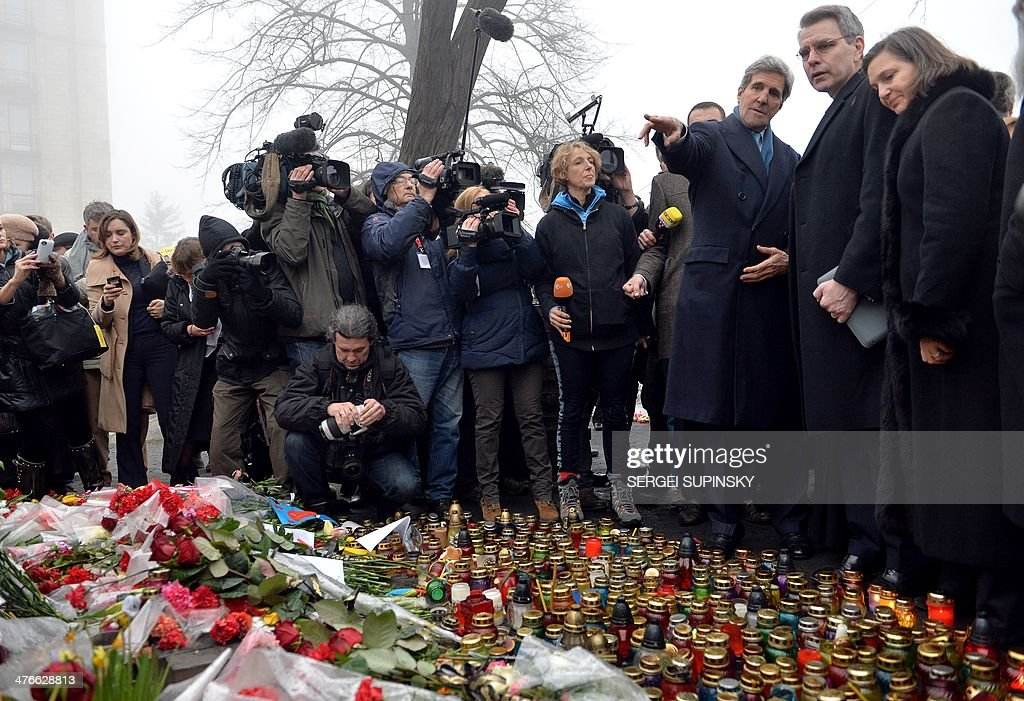 US Secretary of State John Kerry points his finger as he stands with US Assistant Secretary of State for Europe Victoria Nuland (R) and US embassy in Ukraine Geoffrey Pyatt (2nd R) in front of the Shrine of the Fallen, an homage to anti-government protesters who died during the February clashes with anti-riot policemen in Kiev, on March 4, 2014. US Secretary of State John Kerry arrived in Kiev Tuesday for talks with Ukraine's new interim government, amid an escalating crisis in Crimea. His visit came as the United States said it would provide $1 billion to financially-stricken Ukraine as part of an international loan.