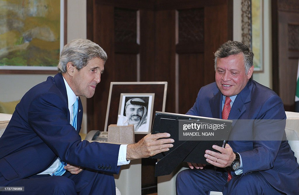 US Secretary of State John Kerry presents a photograph to Jordan's King Abdullah II (R) during a meEting at at the al-Hummar Palace on July 17, 2013 in Amman. Kerry is on his sixth visit to the region as he seeks to persuade the Israelis and Palestinians to resume direct negotiations which broke down almost three years ago. AFP PHOTO/Mandel NGAN