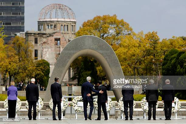 Secretary of State John Kerry puts his arm around Japan's Foreign Minister Fumio Kishida after they and fellow G7 foreign ministers European Union...