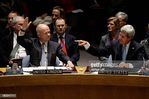 S Secretary of State John Kerry raises a point as British Foreign Secretary William Hague looks on on a resolution regarding Syria's chemical weapons...