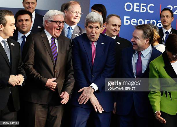 US Secretary of State John Kerry reacts to squeezing into a tight spot with OSCE Chairman Serbian Foreign Minister Ivica Dacic German Foreign...