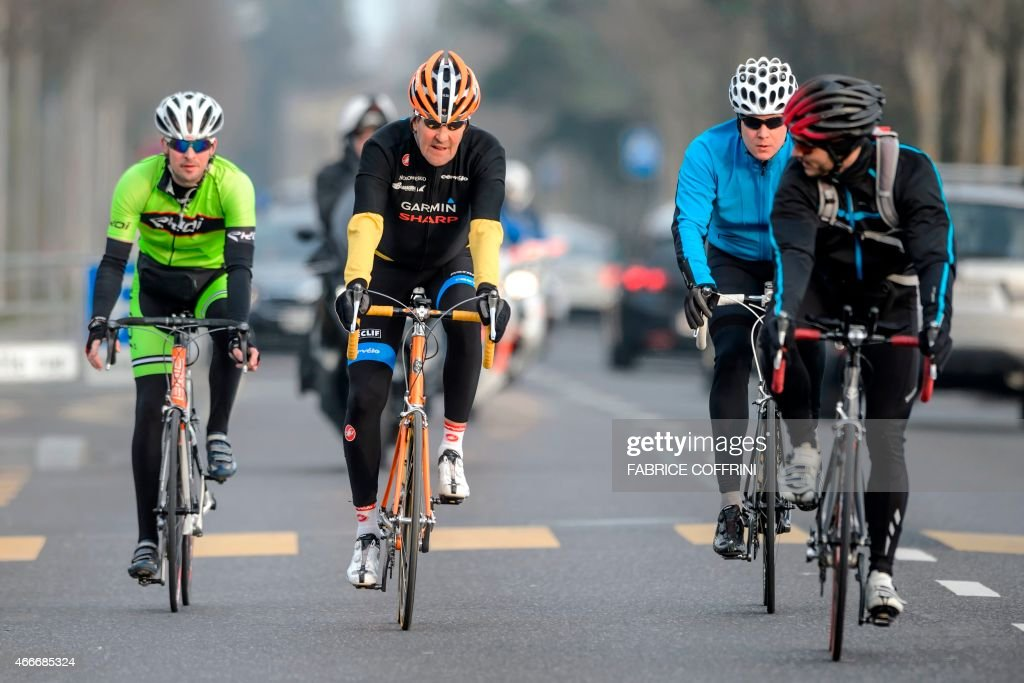 Secretary of State John Kerry (2nd L) rides his bike with bodyguards during a break on Iran talks on March 16, 2015 in Lausanne. US Secretary of State John Kerry has something of a history with broken planes but this week during a break from Iran nuclear talks even his bike needed fixing, a Swiss newspaper reported Wednesday. In what may or may not be a metaphor for the talks in Lausanne, Switzerland Kerry's orange racer on Monday couldn't get into gear properly, Lionel Schumann of the Sam's Bike shop told Le Matin. AFP PHOTO / FABRICE COFFRINI
