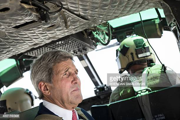 US Secretary of State John Kerry rides in a helicopter September 10 2014 in Baghdad Kerry flew into Iraq today for talks with its new leaders on...