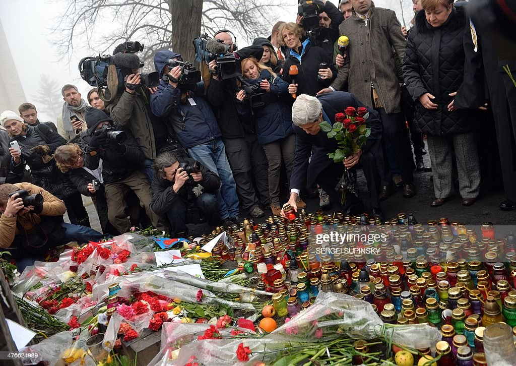 US Secretary of State John Kerry sets a candle to the Shrine of the Fallen, a homage to anti-government protesters zho died during the February clashes with anti-riot policem in Kiev on March 4, 2014. US Secretary of State John Kerry arrived in Kiev Tuesday for talks with Ukraine's new interim government, amid an escalating crisis in Crimea. His visit came as the United States said it would provide $1 billion to financially-stricken Ukraine as part of an international loan.