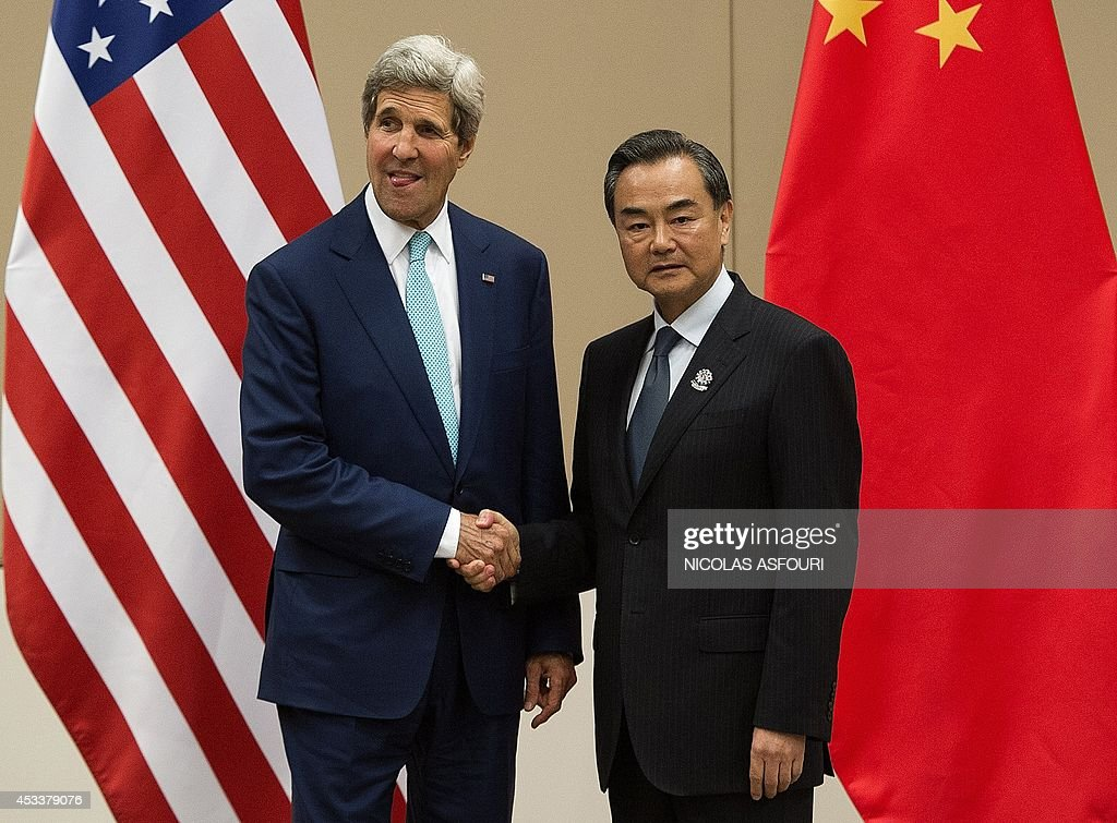 US Secretary of State John Kerry (L) shakes hands with Chinese Foreign Minister Wang Yi (R) during their bilateral meeting on the sidelines of the 47th Association of Southeast Asian Nations (ASEAN) Foreign Ministers' Meeting (AMM) in Naypyidaw on August 9, 2014. Myanmar is hosting the ASEAN Foreign Ministers' Meeting (AMM) and the 21st ASEAN Regional Forum (ARF) from August 8 to 10. AFP PHOTO/ POOL / Nicolas ASFOURI