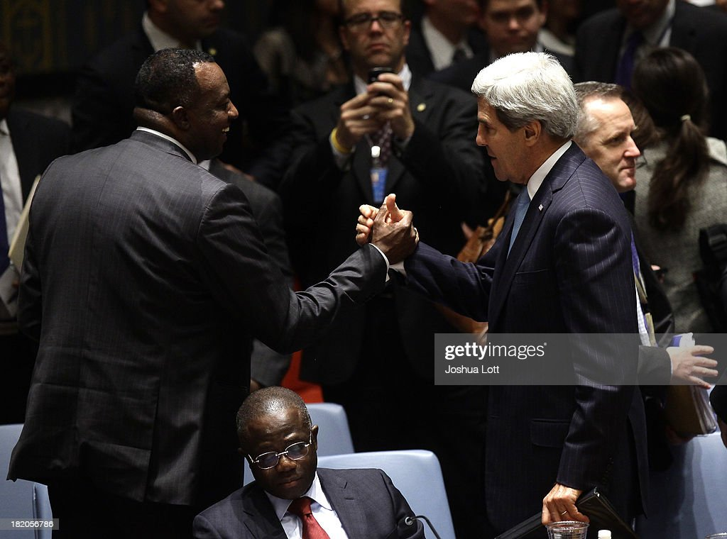 U.S. Secretary of State <a gi-track='captionPersonalityLinkClicked' href=/galleries/search?phrase=John+Kerry&family=editorial&specificpeople=154885 ng-click='$event.stopPropagation()'>John Kerry</a> (R) shakes hands with Rwanda's United Nations Ambassador Eugene Gasana after a U.N. Security Council vote September 27, 2013 at U.N. headquarters in New York City. The Security Council today voted unanimously on a resolution that compels Syria to give up its chemical-weapon stockpile or face consequences. To that end, it requires unfettered access to international chemical-weapons experts, according to published reports.