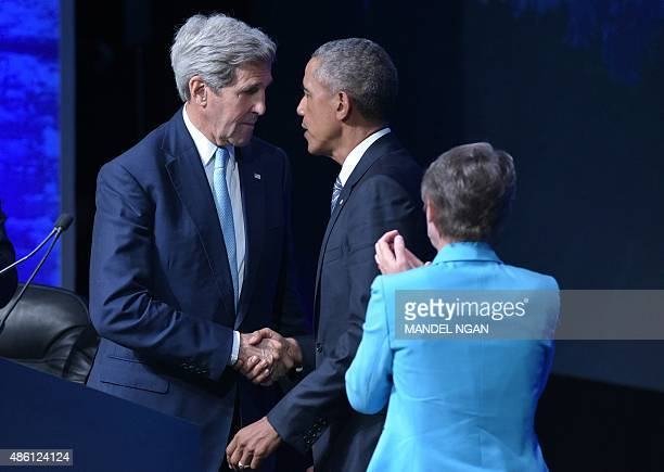 US Secretary of State John Kerry shakes hands with US President Barack Obama as Interior Secretary Sally Jewell applauds after Obama spoke at the...