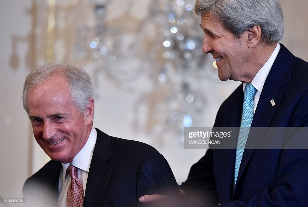 US Secretary of State John Kerry (R) shows the way to Senator Bob Corker, R-TN, for an award presentation ceremony during the release of the 2016 Trafficking in Persons Report on June 30, 2016 at the State Department in Washington, DC . / AFP / Mandel NGAN