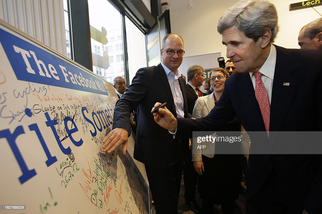 US Secretary of State John Kerry (R) signs a 'Facebook Wall' after speaking at the 'Youth Connect' event in Berlin on February 26, 2013. Kerry visits Berlin as part of a nine-nation tour of US allies in Europe and the Middle East.