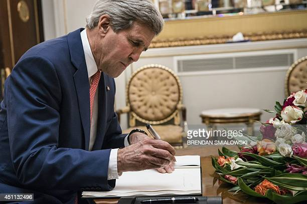US Secretary of State John Kerry signs a guest book before a meeting with Kurdistan regional government president Massud Barzani at the presidential...
