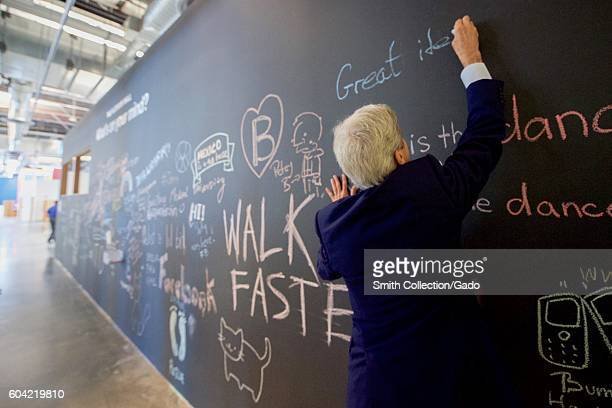 US Secretary of State John Kerry signs a message on the Facebook wall at their new headquarters in Menlo Park California before meeting with CEO Mark...