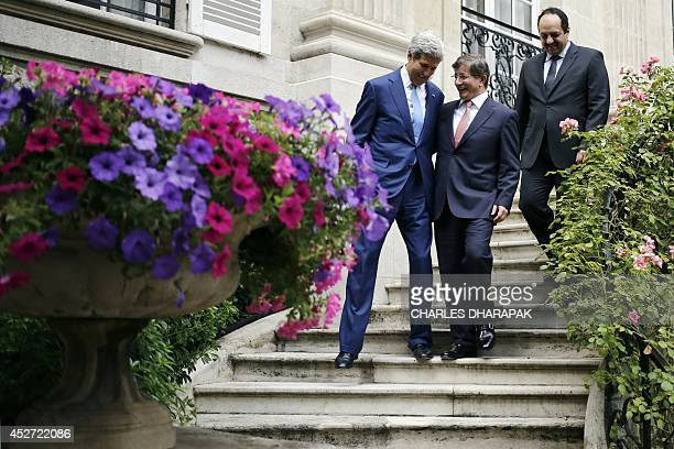 US Secretary of State John Kerry speaks to Turkish Foreign Minister Ahmet Davutoglu and Qatari Foreign Minister Khaled alAttiyah as they walk down...
