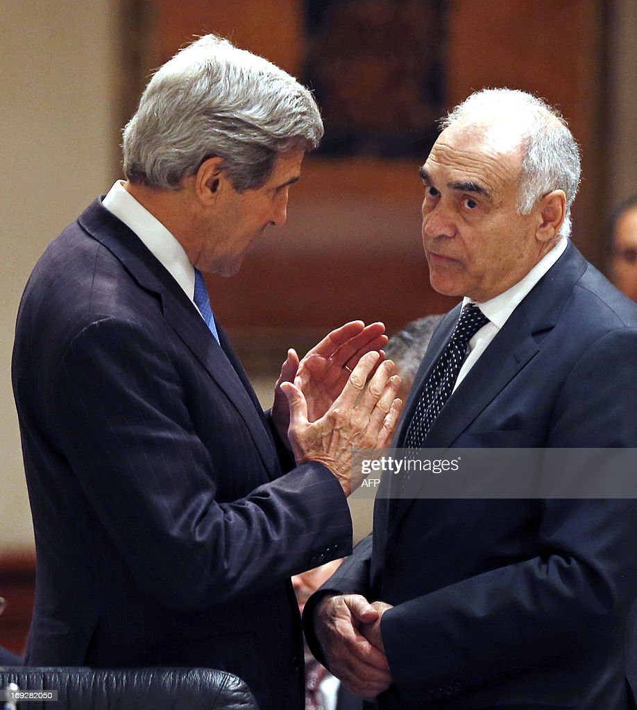 US Secretary of State John Kerry (L) speaks with Egyptian Foreign Minister Mohamed Kamel Amr prior to the opening of the 'Friends of Syria' meeting in Amman, Jordan on May 22, 2013. The gathering seeks to discuss US-Russian proposal to hold a peace conference dubbed 'Geneva 2' to bring together rebels and representatives of Syrian President's regime.