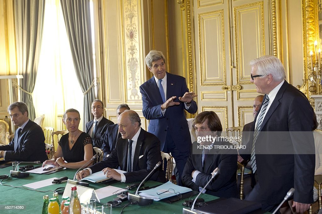 US Secretary of State John Kerry speaks with German Foreign Minister FrankWalter Steinmeier behind French Foreign Affairs minister Laurent Fabius...